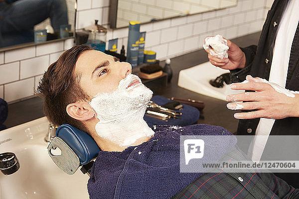Barber shaving mid adult man.
