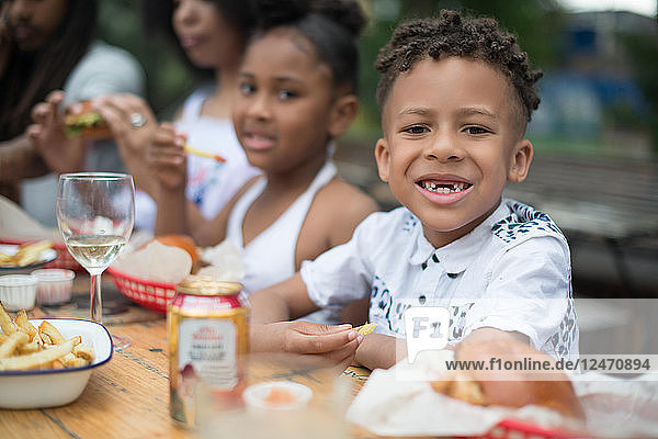 Boy eating with family at outdoor restaurant