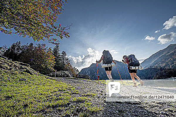 Young women hiking on trail under sunshine