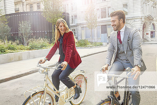 Young couple riding bicycles on street