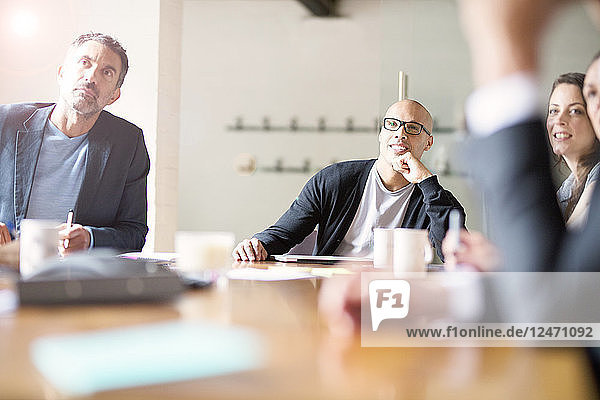 Businessman with glasses listening during meeting in conference room