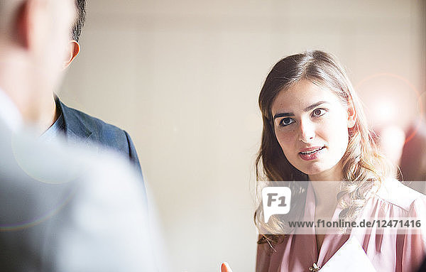 Young businesswoman talking to colleagues in office