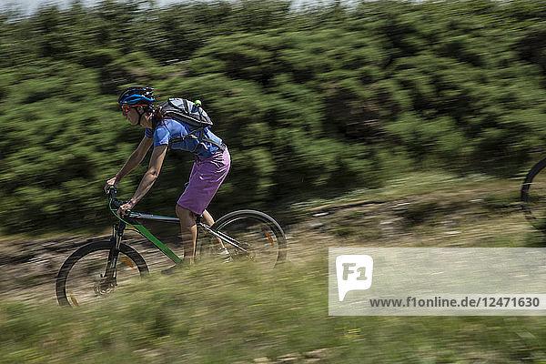 Woman mountain biking through field in Porlock Weir  England