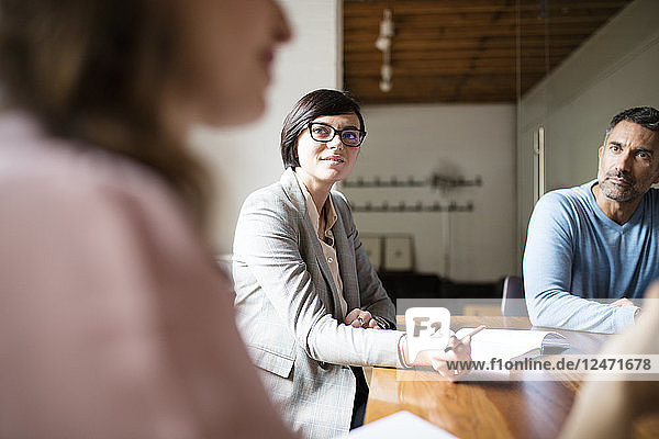 Businesswoman with glasses listening to colleague during meeting