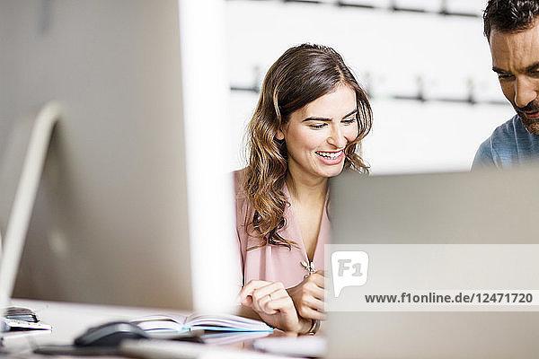 Lächelnde junge Geschäftsfrau hört einem Kollegen am Schreibtisch im Büro zu
