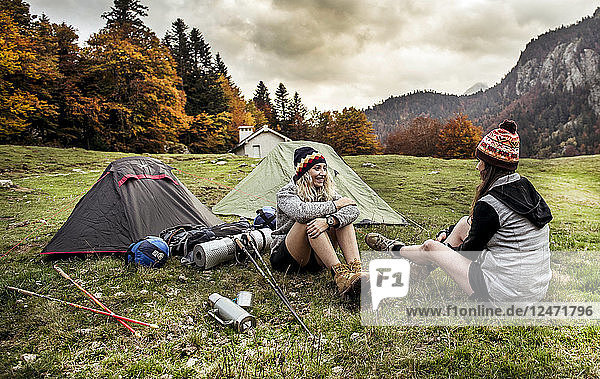 Young woman talking with friend while camping