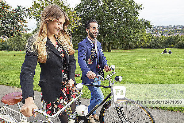 Young couple walking bicycles in park