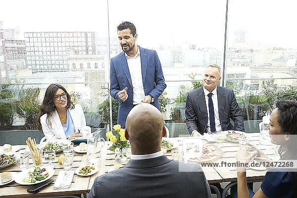 Businessman giving speech during restaurant meeting