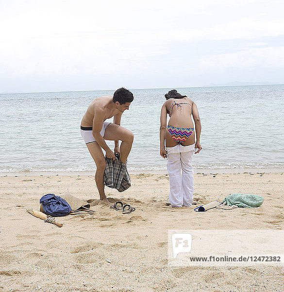 Young people undressing on beach
