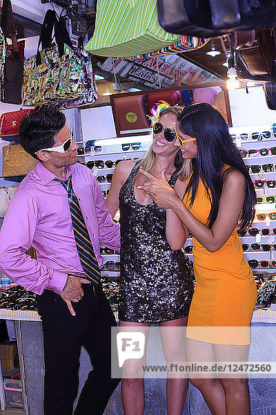 Friends trying on sunglasses at night
