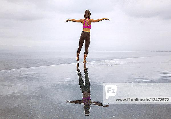 Young woman balancing on infinity pool
