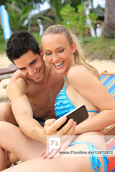 Young couple taking selfie on beach