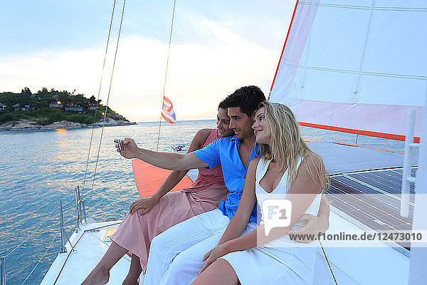 Friends taking selfie on yacht at sunset