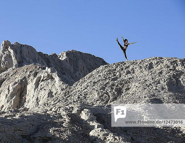 Young woman kicking on mountain rock