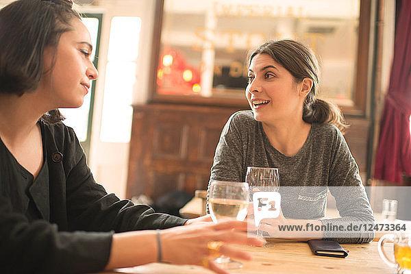 Young women talking at bar
