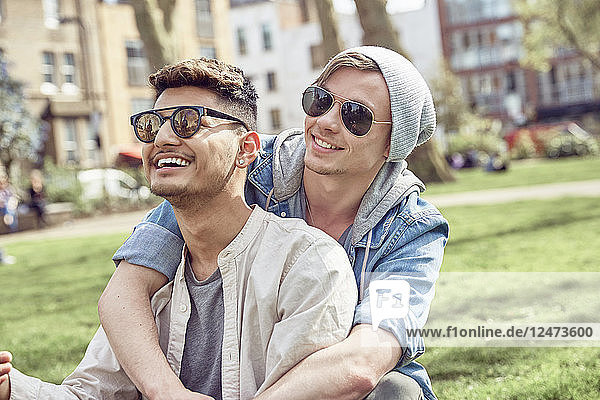 Gay teenage couple sitting together in park
