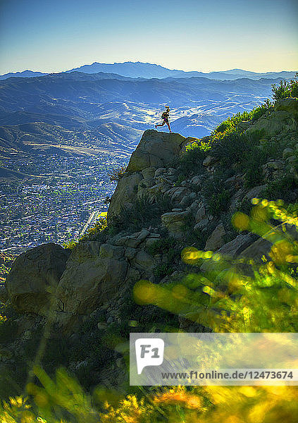 Young woman running on mountain rocks