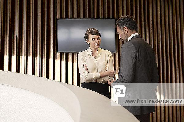 Woman talking to man by concrete balustrade