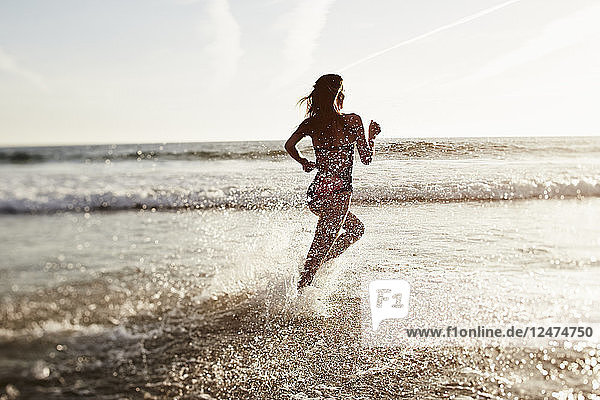 Young woman running in sea