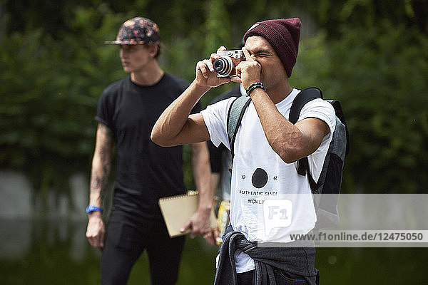 Teenage boy taking photograph with camera