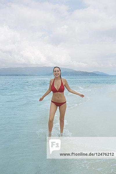 Young woman wearing bikini standing in sea