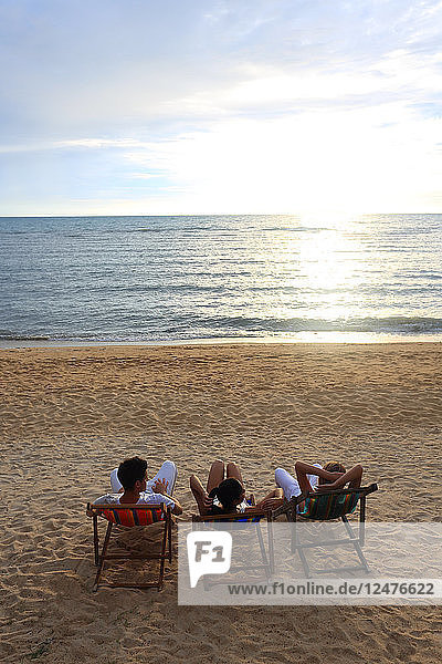 Young people sitting on deck chairs on beach