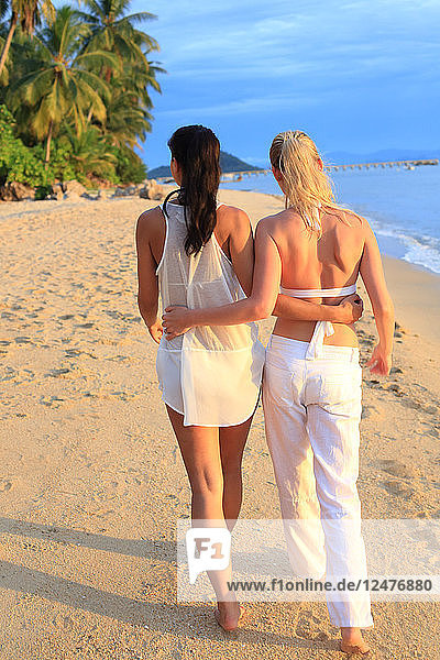 Young couple wearing white walking on beach