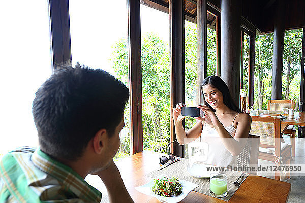 Young woman photographing young man at table