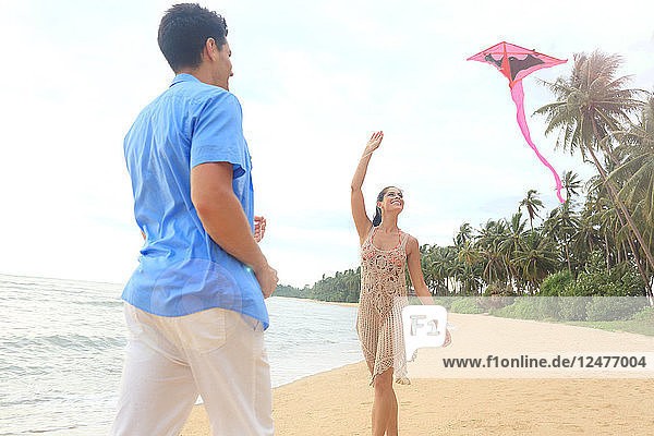 Young couple flying kite on beach