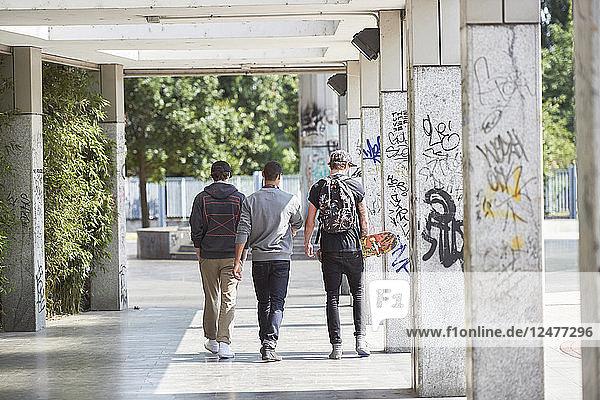 Teenage boys walking by graffitied pillars