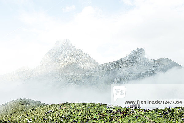 People hiking in mountain field