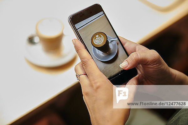 Hands of woman photographing coffee with smart phone