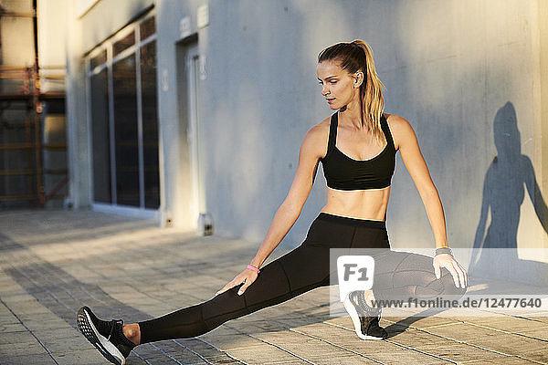 Woman wearing black sportswear stretching
