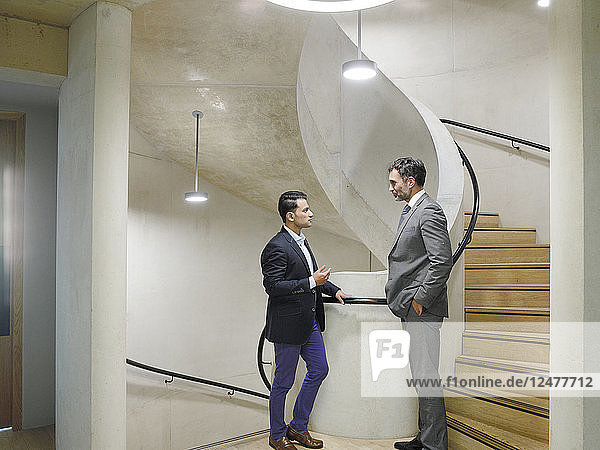 Men in suits talking on staircase at Blavatnick School of Government