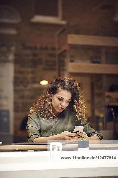 Junge Frau benutzt Smartphone hinter dem Fenster eines Cafés