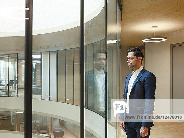Young man in suit by window at Blavatnik School of Government