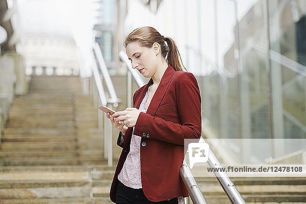Mid adult woman using smart phone on staircase