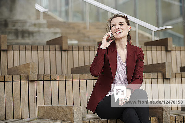 Mid adult woman on phone on staircase