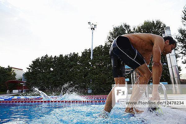 Man exiting swimming pool