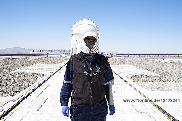 Masked scientist by telescope at Paranal Observatory