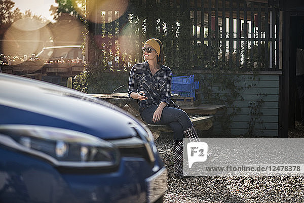 Woman sitting at picnic table by car