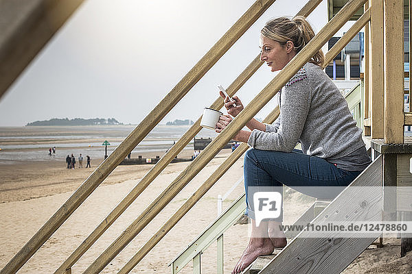 Woman holding smart phone and mug on beach