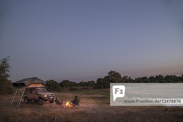 Tourists by camp fire and safari 4x4 in South Luangwa National Park  Zambia