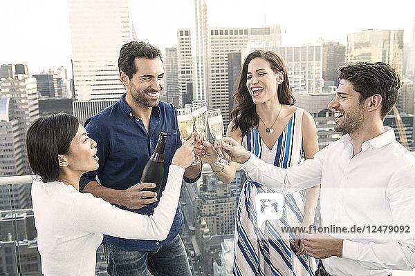 Freunde stoßen auf einem Balkon während einer Party in New York City an