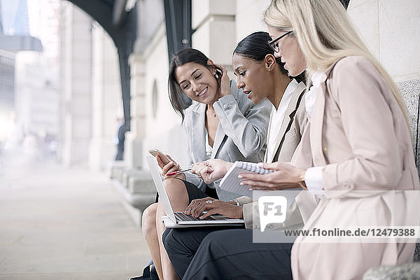 Businesswomen using technology on bench