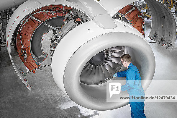 Man working on airplane engine in hangar