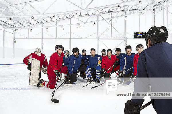 Group of ice hockey players kneeling on ice rink