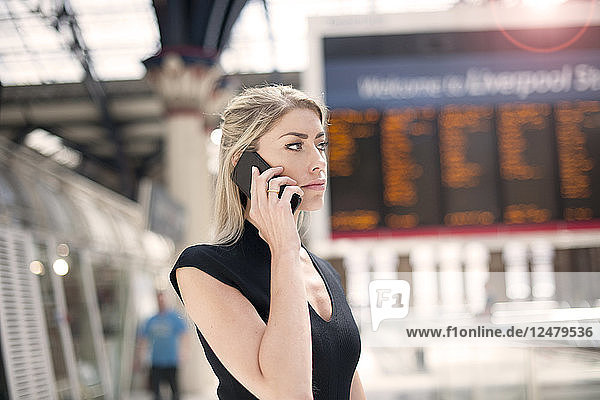 Businesswoman on phone in train station