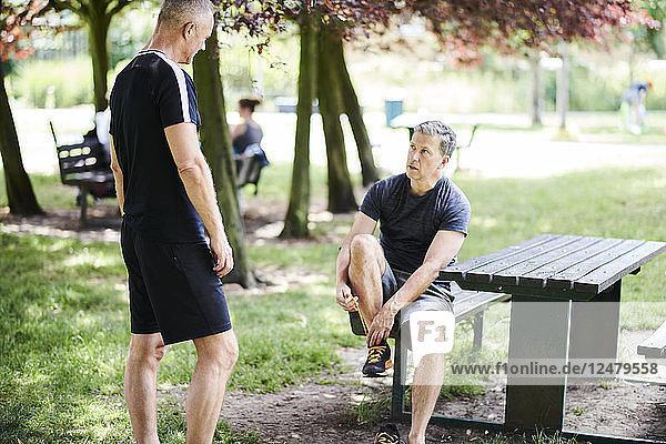 Mature man tying shoe on picnic table