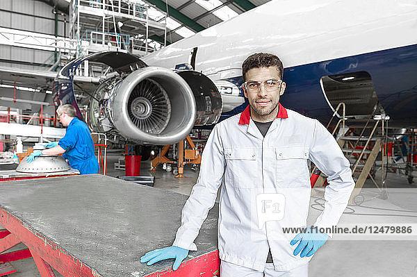 Porträt eines jungen männlichen Arbeiters in einem Flugzeughangar